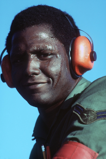 A ground crewman, wearing noise protectors, participates in Exercise VOLANT RODEO 1984. PHOTO from November 84 AIRMAN Magazine