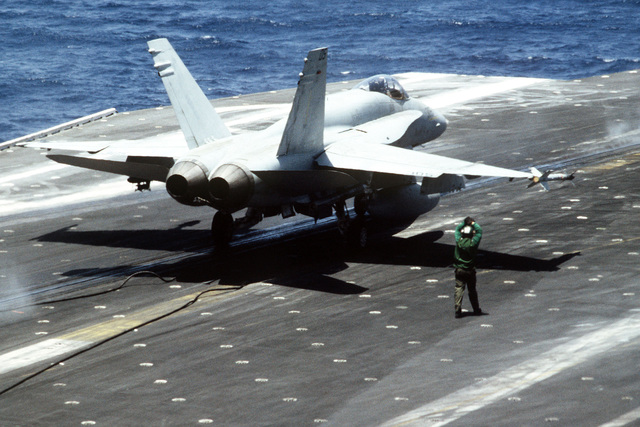 A hook releaseman signals downlock instructions after the arresting cable has been disengaged from an F/A-18A Hornet aircraft aboard the aircraft carrier USS CONSTELLATION (CV 64). The Strike Fighter Squadron 25 aircraft is armed with an ATM-9 Sidewinder air-to-air missile on the right wing tip and an ATM-7 Sparrow air-to-air missile on the right nacelle fuselage station
