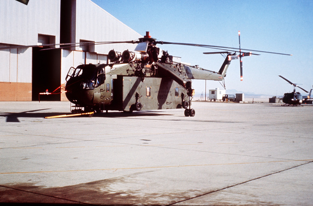 A left side ground view of CH-54 Tarhe helicopter with the universal military pod, an all-purpose van complete with communications, ventilation, lighting systems and ground wheels
