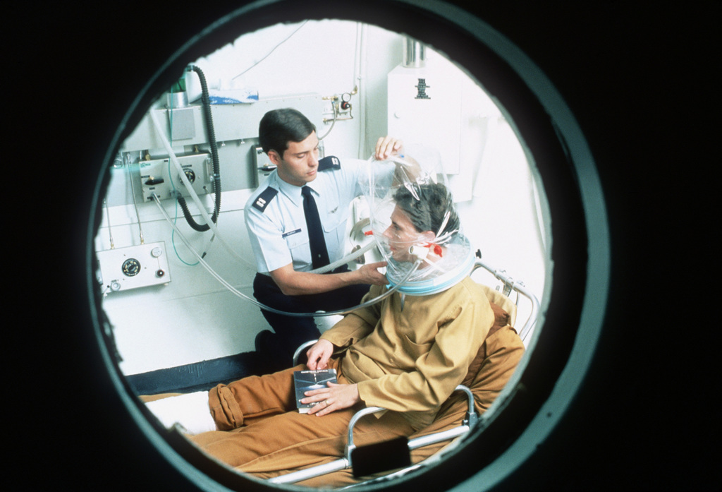 A patient is treated in a hyperbaric chamber. August 84 AIRMAN Magazine