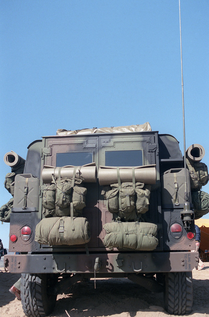 A rear view of a US Army M998 High-Mobility Multipurpose Wheeled Vehicle equipped with an M2 .50 caliber machine gun. Field packs are attached on the rear of the vehicle
