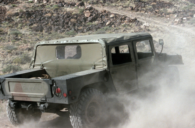 A right rear view of a US Army M998 High-Mobility Multipurpose Wheeled Vehicle traveling across rough terrain during testing