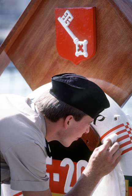 A sailor cleans a life ring aboard a foreign ship participating in exercise Ocean Safari '85