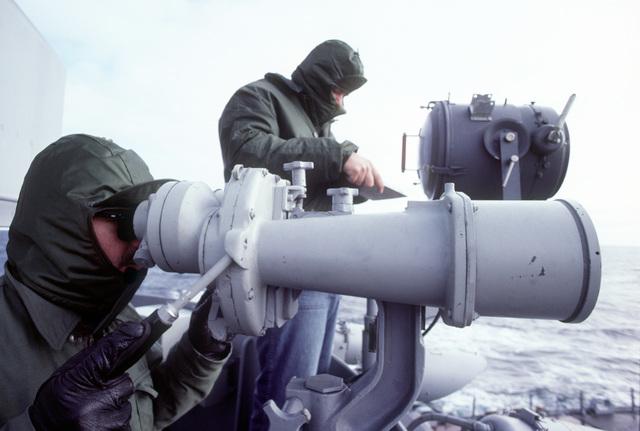 A sailor looks through a pair of high-powered binoculars during exercise Ocean Safari '85