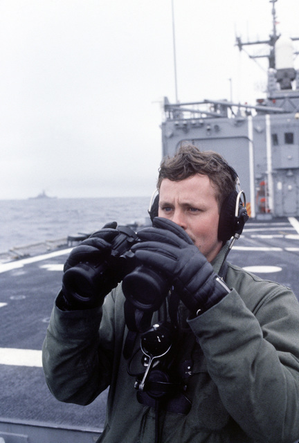 A sailor on the fantail of the guided missile frigate USS HALYBURTON (FFG-40) searches for aircraft during exercise Ocean Safari '85