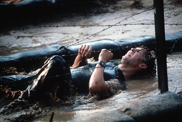 A security policeman maneuvers under barbed wire on a very muddy portion of the obstacle course during Exercise Volant Rodeo '84
