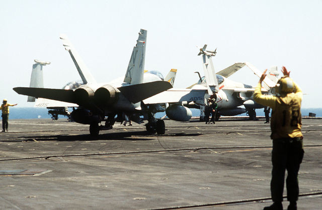 A Strike Fighter Squadron 25 F/A-18A Hornet aircraft stands by on the flight deck of the aircraft carrier USS CONSTELLATION (CV 64). The aircrft is armed with an ATM-9 Sidewinder air-to-air missile on the right wing tip. A plane director on the right signals taxi instructions. An A-6E Intruder aircraft is in the background