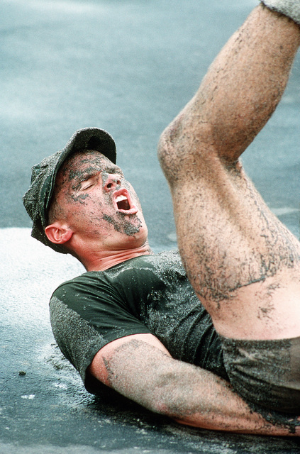 A Third Phase Basic Underwater Demolition/SEAL (BUD/S) student, turned sugar cube by surf and sand, works through the pain of flutter kicks during physical training (PT) at the Naval Special Warfare Center