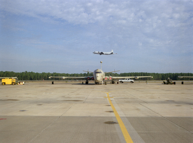 A United Kingdom Royal Navy Nimrod recon and patrol aircraft sits on the tarmac. The 120th CSX Squadron, RAF Kinloss, England maintains a four plane detachment at Jacksonville. The wing tips of two other Nimrods can be seen to the left and right. In the background, a P-3AC Orion aircraft is taking off in the background