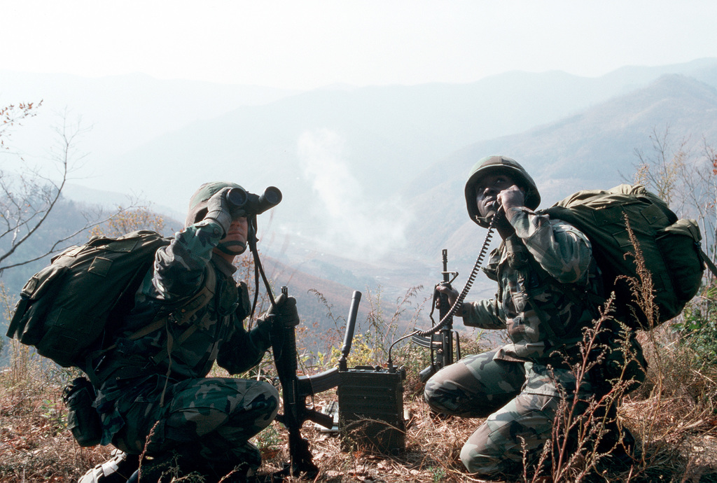 """A USAF SENIOR AIRMAN Scott Hays (left) and STAFF Sergeant Larry St. Clair Jr., both enlisted terminal attack controllers stationed at Camp Casey, South Korea but assigned to the 51st Fighter Wing, Osan Air Base, South Korea use a portable radio to call in air-strikes. From AIRMAN Magazine's January 1995 issue article """"Keeping an Eye on the Bad Guy"""""""