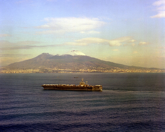 Aerial port beam view of the nuclear-powered aircraft carrier USS NIMITZ (CVN-68) underway. Mount Vesuvius, Italy, is in the background