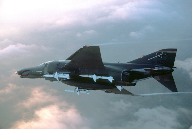 Air-to-air left side view of an F-4E Phantom II fighter aircraft assigned to the 52nd Tactical Fighter Wing, Spangdahlem Air Base, Germany. Mounted on the front underside portion of the wings are two AGM-45A Shrike air-to-surface missiles. Two AIM-7 Sparrow III air-to-air missiles are mounted towards the rear. The aircraft is equipped with an electronic countermeasures (ECM) pod