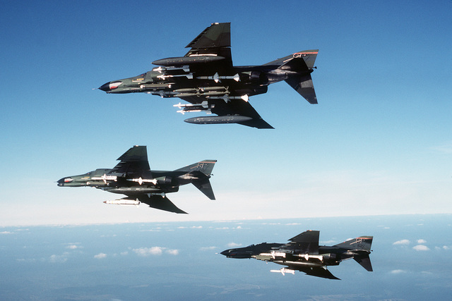 Air-to-air left side view of two F-4E Phantom II and an F-4G Phantom II Advanced Wild Weasel aircraft (center) from the 52nd Tactical Fighter Wing, Spangdahlem Air Base, Germany. The aircraft are armed with an AGM-78 Standard anti-radiation missile (F-4G), AGM-45 Shrike air-to-surface missiles, AIM-7 Sparrow III and AIM-9 Sidewinder air-to-air missiles. The aircraft are equipped with electronic countermeasures (ECM) pods. The F-4E aircraft (top foreground) is armed with four MK 82 general purpose bombs