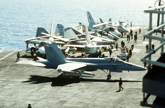 An F/A-18A Hornet aircraft from Strike Fighter Squadron 25 taxis on the flight deck of the aircraft carrier USS CONSTELLATION (CV 64). The aircraft is armed with an AIM-9 Sidewinder air-to-air missile on the right wing tip and an AGM-45 Shrike air-to-surface anti-radiation missile on the right outboard wing pylon. Aircraft parked in the background include S-3 Vikings, A-6E Intruders and F/A-18A's