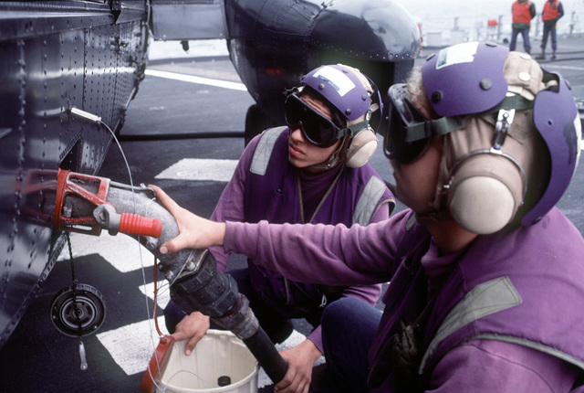 Aviation fuels technicians refuel a helicopter on the deck of a ship during exercise Ocean Safari '85