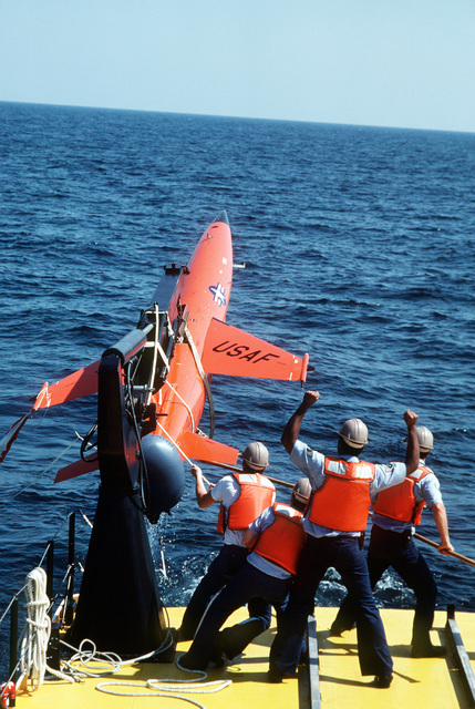 Crew members of the 82nd Tactical Aerial Targets Squadron use a hoist to lift a BQM-34F Firebee II target drone aboard a drone recovery boat. AIRMAN Magazine-December 1984