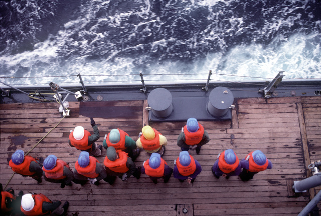 Crewman muster on deck aboard the battleship USS IOWA (BB-61) prior to an underway replenishment during exercise Ocean Safari '85