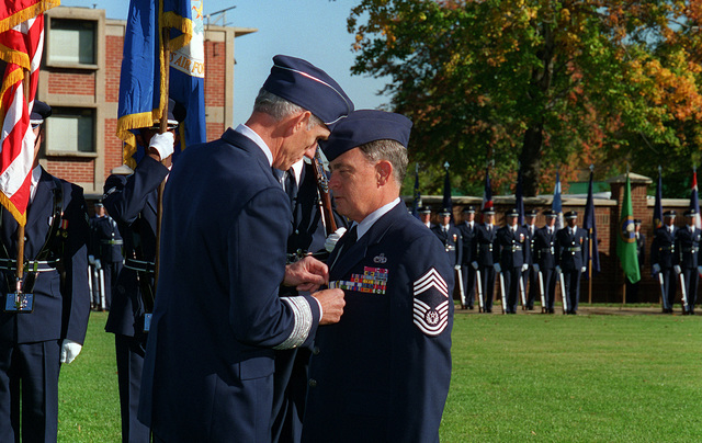 GEN. Merril A. McPeak, Air Force CHIEF of STAFF, pins the distinguished service medal on CHIEF MASTER SGT. of the Air Force, Gary Pfingston, at his retirement on the ceremonial lawn