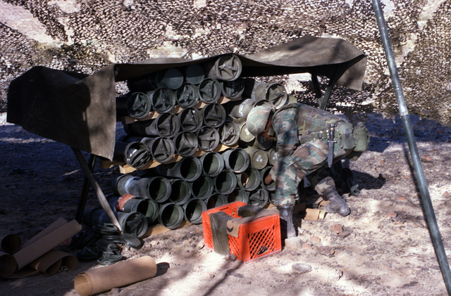 Gun crewmen bending over in front of a rack of powder canisters. Rack is under a low, canvas covered frame. Camouflage netting in background