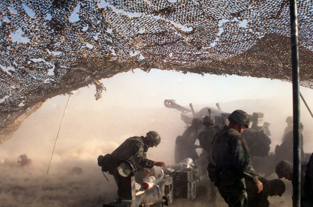 Left rear view, camera under camouflage netting. An M198 155 mm Howitzer, muzzle flash and smoke. Gun crewmen in foreground
