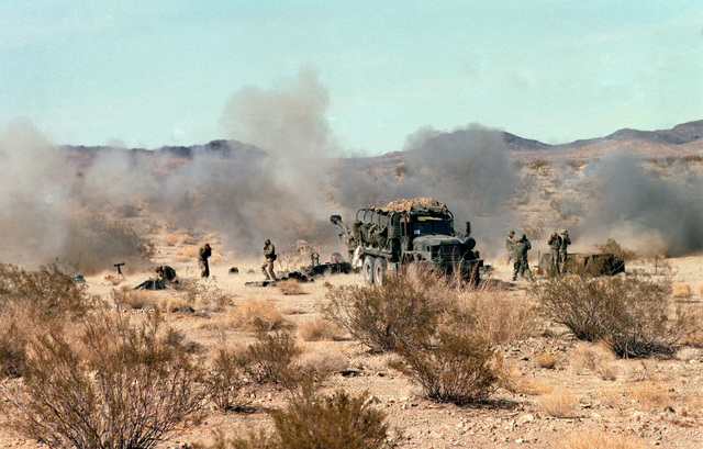 Long shot, front view, M813 5 ton truck. M198 155 mm Howitzer, cloud of smoke in front of muzzle, is partially visible behind vehicle. Gun crewmen on either side of truck. Desert underbrush in foreground and mountain range in background