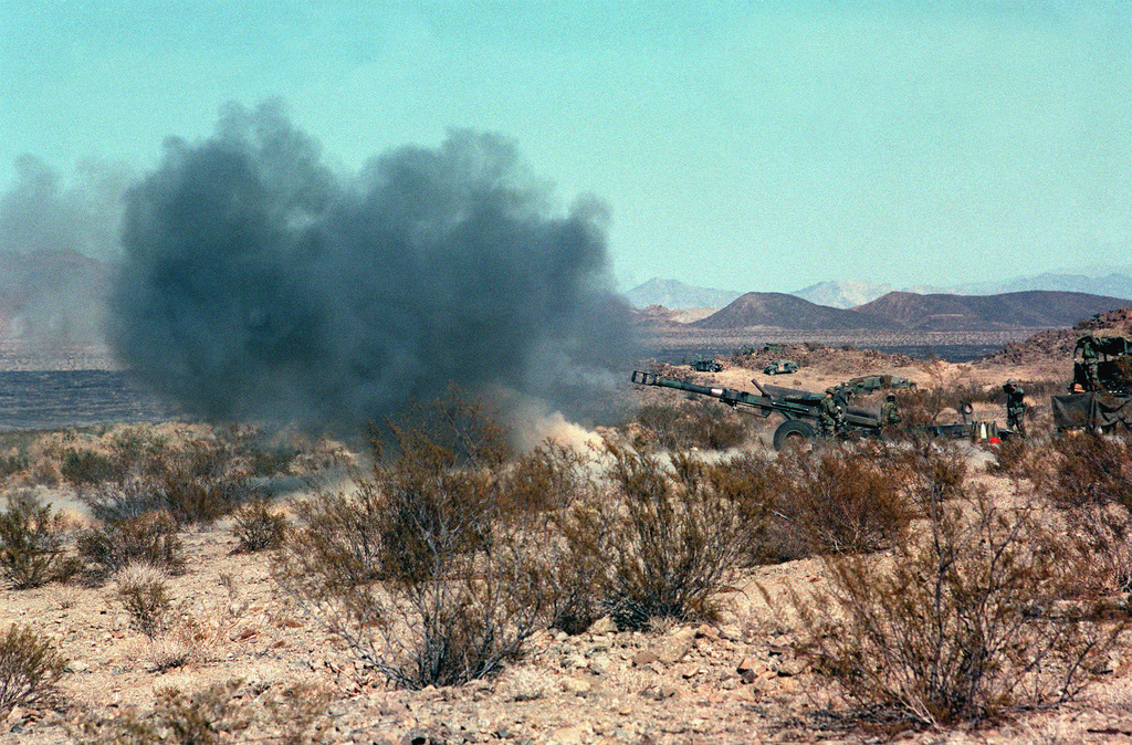 Long shot, left side view, M198 155mm Howitzer cloud of smoke in front of muzzle. M813 5 ton truck, rear half only, behind howitzer. Desert underbrush in foreground and mountain range in background