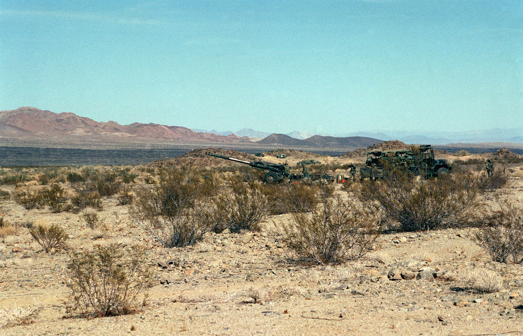 Long shot, left side view, M198 155mm Howitzer in firing position. M813 5 ton truck behind howitzer. Desert underbrush in foreground and mountain range in background