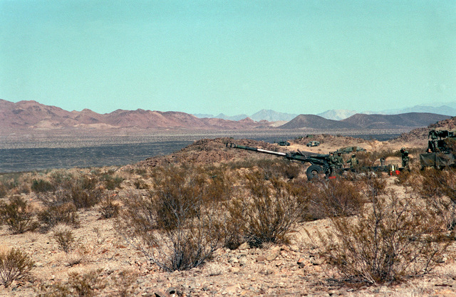 Long shot, left side view, M198 155mm Howitzer in firing position. M813 5 ton truck, rear half only, behind howitzer. Desert underbrush in foreground and mountain range in background