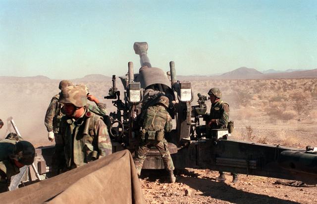Rear view, several gun crewmen, one holding lanyard, around breach of an M198 155 mm Howitzer. Desert terrain in background,
