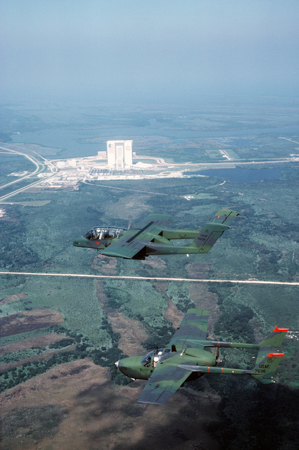 Right top view of an OV-10 Bronco aircraft, background, and an O-2 Skymaster aircraft flying past the Kennedy Space Center at Cape Canaveral Air Force Station. PHOTO from November 84 AIRMAN Magazine