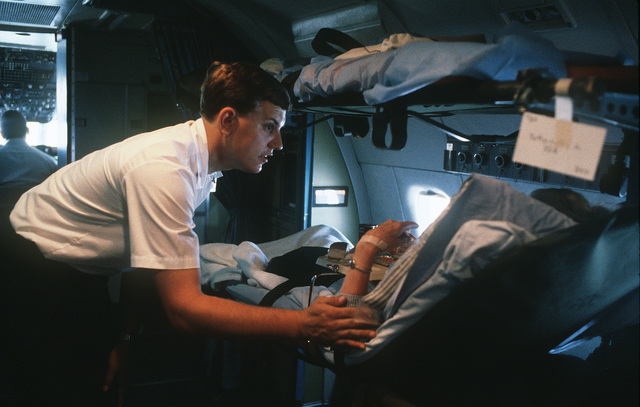 SENIOR AIRMAN (SRA) Jeff R. McKenzie of the 57th Aeromedical Evacuation Squadron comforts a patient during a flight to Buckley Field, Colorado aboard a C-9 Nightingale aircraft. From the February 1985 AIRMAN Magazine