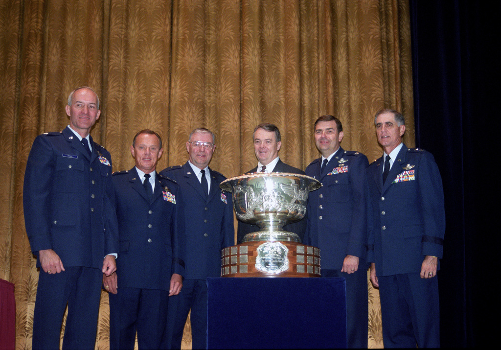 """U.S. Air Force North Dakota Air National Guard Airmen, from the 119th Fighter Wing""""Happy Hooligans"""", win the prestigious Huges Trophy, which recognizes the most outstanding air-to-air unit in the U.S. Air Force. From left to right Brig. GEN. Thomas Hruby; An unidentified Air Force Officer; MAJ. GEN. Keith Bjerke; A representative from McDonald Douglas; An unidentified Air Force Officer; COL. Michael J. Haugen; and MAJ. GEN. Donald Shepperd, Director of the Air National Guard. (A3604) (U.S. Air Force PHOTO by TECH. SGT. David H. Lipp, 119th Communications Flight) (Released)"""