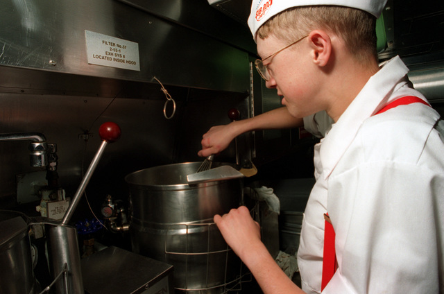 A mess specialist cook prepares soup for the crews afternoon meals on the crews galley on board the nuclear-powered attack submarine USS ASHEVILLE (SSN-758) while underway off San Diego