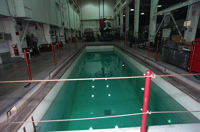 A view inside the Deep Submergence Unit training pool building. In the right rear background is the Avalon (DSRV-2) Deep Submergence Rescue Vehicle resting on its transport trailer