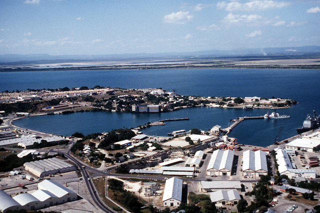 An aerial view of Naval Base Guantanamo Bay's windward side looking southwest with Corinaso Point in the middle and McCalla Airfield in the background. Tents for Cuban migrants are visible on McCalla Field
