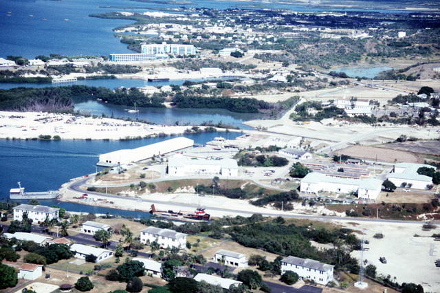An aerial view of Naval Base Guantanamo Bay's windward side. The Port Services Boat Shed is visible at the water's edge on the left; the Base Chapel is visible near the upper right side of the photo; the green and white buildings in the upper left are part of the Deer Point Bachelor's Officer's Quarters (BOQ)