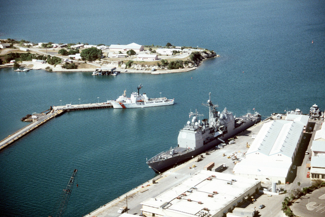 """An aerial view of Naval base Guantanamo Bay's windward side with the guided missile cruiser USS MONTEREY (CG-61) tied up at Wharf """"B"""" and the medium endurance cutter USCG COURAGEOUS (WMEC-622) at Pier """"C"""""""