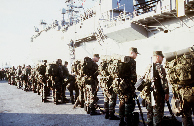 Marines from Battalion Landing Team 36 wait to embark the USS AUSTIN (LPD-4) for deployment to Guantanamo Bay, Cuba. The team will be augmenting the existing security force in Guantanamo Bay in anticipation of the arrival of Cuban refugees from Panama