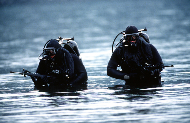 Two 62nd Combat Controllers in full scuba gear carry M-16's and wade through water up to their waists during water stealth operations