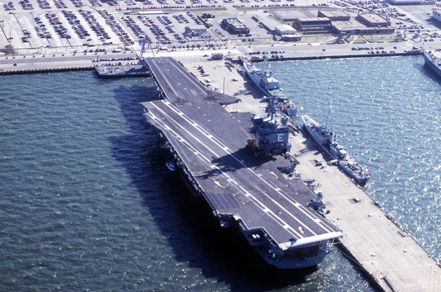 An aerial port quarter view of the nuclear-powered aircraft carrier USS ENTERPRISE (CVN-65) tied up on the north side of pier 11. On the south side of the pier 11 is two visiting Canadian frigates, the HMCS Nipion (DDE-266) and the HMCS TERRA NOVA (DDE-259)