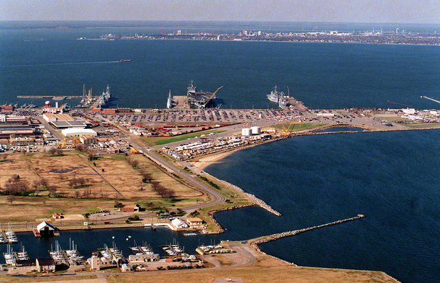 An aerial view, looking west, of a portion of the Norfolk Naval Base covering the area of piers 10 to 12. The nuclear-powered aircraft carrier USS ENTERPRISE (CVN-65) is moored to the north side of pier 11 with two visiting Canadian frigates on the south side. The city and shipyard at Newport News is located on the peninsula in the background