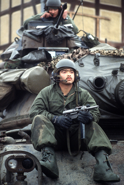 Private First Class (PFC) Jose Ledoux-Garcia of Company C, 5th Battalion, 77th Armor, guards his M60A3 main battle tank during Central Guardian, a phase of Exercise REFORGER '85. He is armed with an M3A1 .45-caliber submarine gun