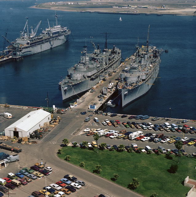 Aerial port bow view of the submarine tenders USS SPERRY (AS 12), right, and USS PROTEUS (AS 19) docked at Ballast Point. The submarine tender USS DIXON (AS 37) is docked far left