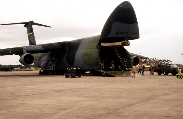 A right side view of a US Air Force C-5 Galaxy from the 3rd Airlift Squadron, Dover Air Force Base, Del., as its cargo is unloaded on the ramp at the airport. US Air Force aircraft are bringing in material and equipment to support the withdrawal of United Nations peacekeepers