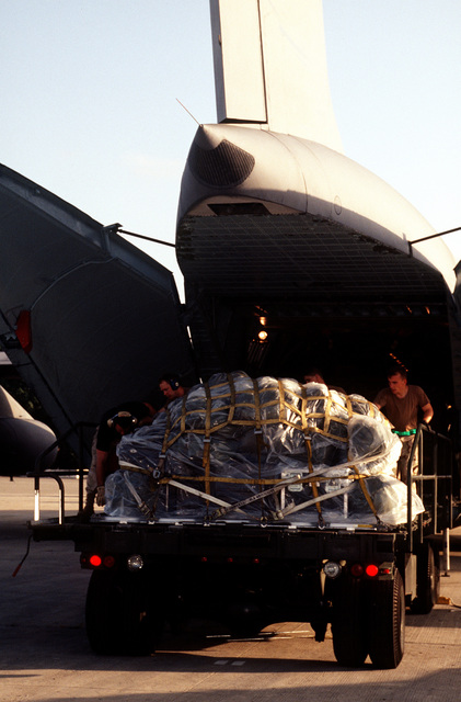 Equipment and supplies are being unloaded from a US Air Force C-5 Galaxy from the 3rd Airlift Squadron, Dover Air Force Base, Del., on the ramp at the airport. US Air Force aircraft are bringing in material and equipment to support is the withdrawal of United Nations peacekeepers