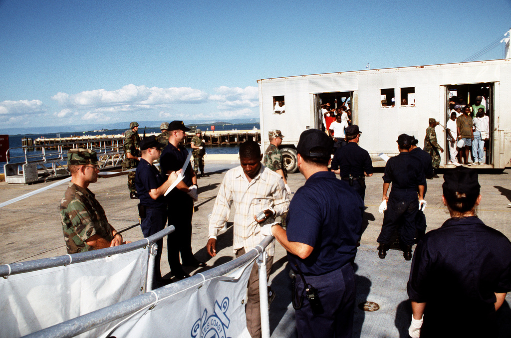 A voluntary Haitian repatriate passes a security team and approaches the ramp of a Coast Guard Cutter to be transported back to Haiti