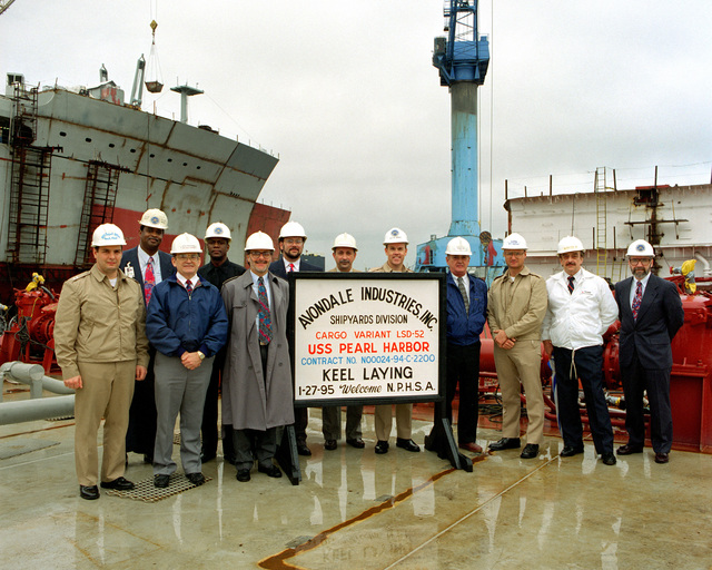 The official party at the keel laying of the dock landing ship Pearl Harbor (LSD-52). (L-R) LT. Frank Simei, Proj. Officer; H.J. Brown, Hull Mgr; A.J. Thibodeaux, Proj. Mgr; T.E. Johnson, Asst. Hull Mgr; Carey Agregaard, Asst. Program Mgr; James Roemer, CHIEF Engineer; Louis Duet, Asst. Configuration Mgr; CDR. James L. Jenkins, USN, Supervisor of Shipbuilding; Ronnie Clark, Lead Production Engineer; LCDR. Bill Salinas, USN, Project Officer; David Gordon, Program Mgr; Bernard P. Clark, Deputy Supervisor of Shipbuilding