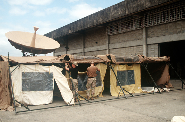 Personnel with the 16th Special Operation Squadron, Hurlburt Field, Florida, work on setting up a temper tent to be used as their operations center at an airport in east Africa. A satellite dish is located behind the tent. US Air Force aircraft are bringing in materiel and equipment to support the operation which is the withdrawal of the United Nations' peacekeepers from Mogadishu, Somalia