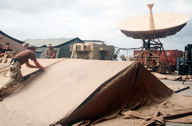 Personnel with the 16th Special Operation Squadron, Hurlburt Field, Florida, work on setting up a temper tent to be used as their operations center at an airport in east Africa. An AN/TSC-100A satellite ground station is in the background. US Air Force aircraft are bringing in materiel and equipment to support the operation which is the withdrawal of the United Nations' peacekeepers from Mogadishu, Somalia
