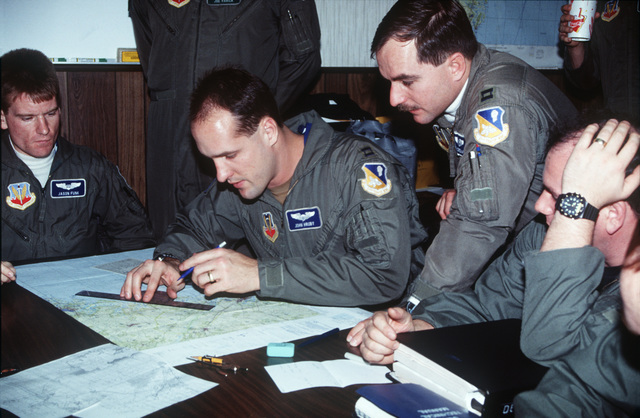 Captains Jason Funk (left), John Hruby, and Bruce Edwards (right), members of the 523rd Fighter Squadron, Cannon Air Force Base, New Mexico, prepare their flight plans